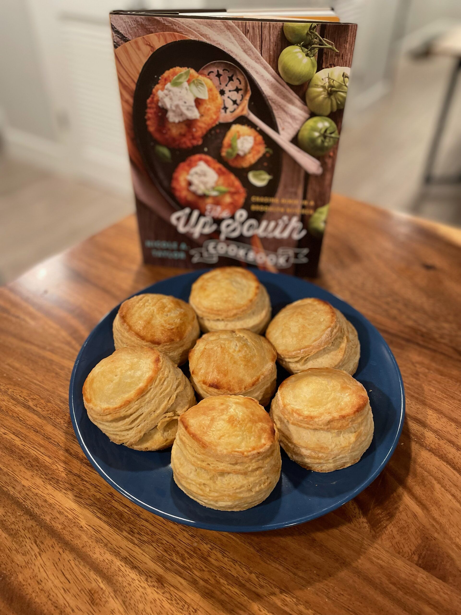 The Up South Cookbook with a plate full of buttermilk biscuits