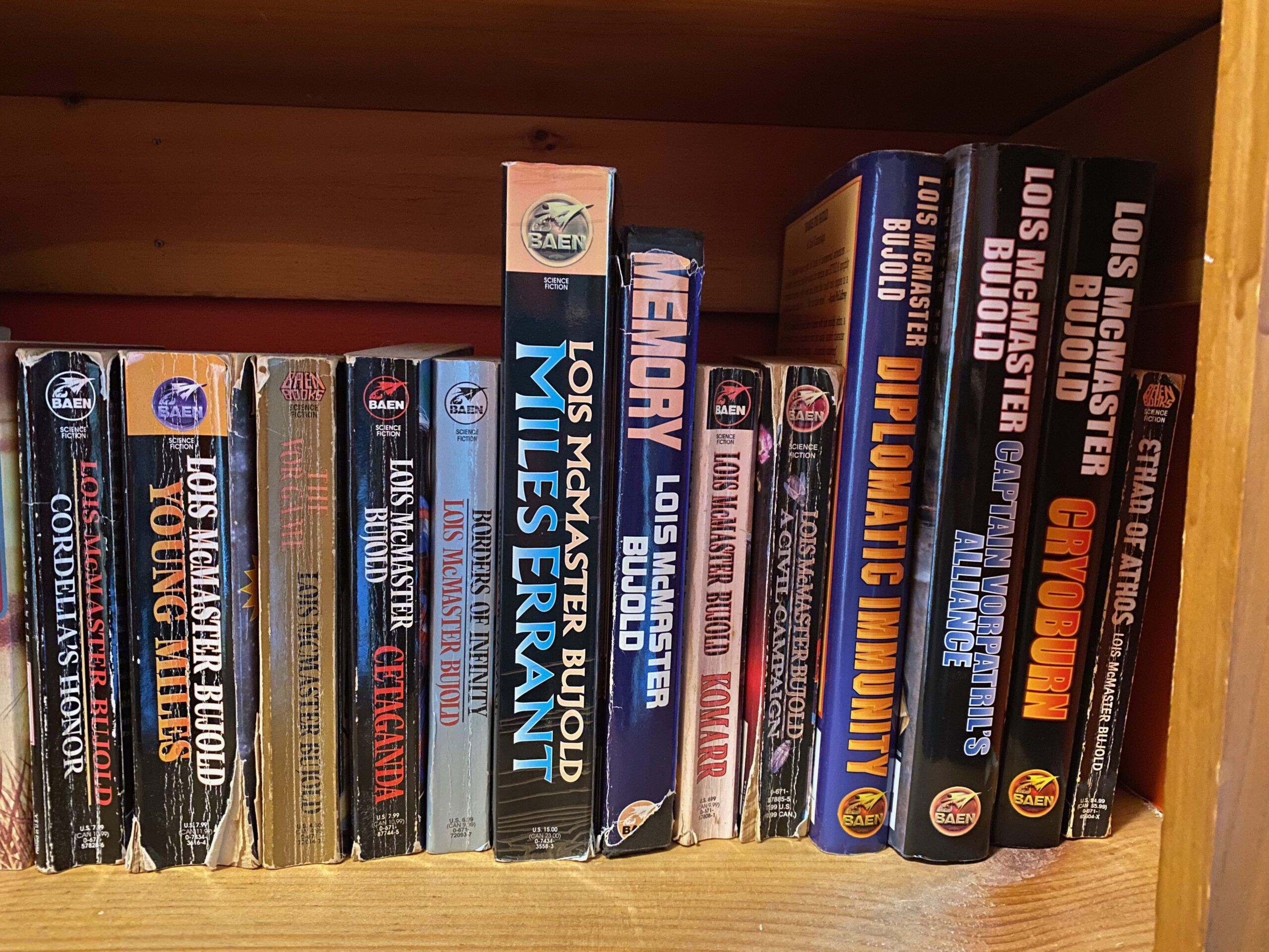 The books in the Vorkosigan Saga lined up on a bookshelf. They are mostly well-worn mass market paperbacks. (Photo taken by me)