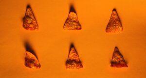 six individual Doritos chips against an orange background