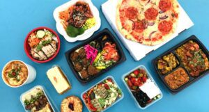 assortment of foods in takeout containers against a blue backdrop