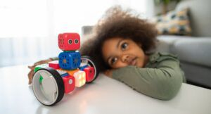 Image of a young Black girl looking at a toy robot
