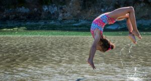 image of young girl flipping in a lake