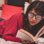 Image of a dark haired woman reading on a bed