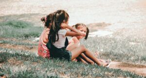Image of three kids sitting in the grass