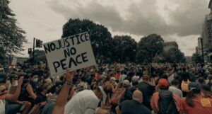 image of a large protest. Someone is holding a sign that reads No Justice, No Peace