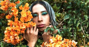 a trans woman surrounded by green plants holding yellow flowers
