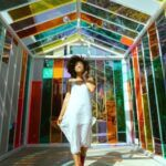 image of woman walking through colorful stained glass hallway