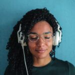 a person with their eyes closed wearing a pair of white over-ear headphones