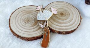 An enamel pin depicting a brown hand holding an open book stylized as a flower, with pink butterflies