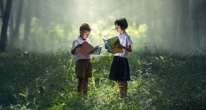 two children reading a book in a green wooded area