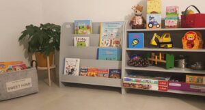 a kids reading nook including a plant, two kids size bookshelves, and a basket of books