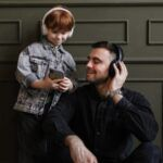 a child and adult both wearing headphones and looking at a mobile phone