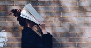 a person holding a book up to their face