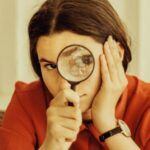 vintage style image of a girl with brown hair and olive skin holding a magnifying glass