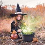 kid dressed up as a witch with cauldron