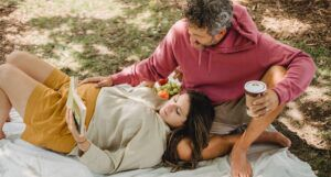 a photo of a couple on a picnic blanket reading. One is pregnant