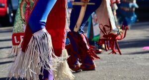 the legs of people doing a traditional Mexican dance in a parade